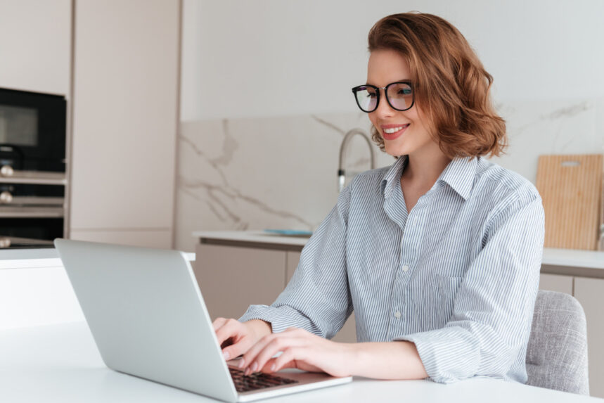 elegant smiling woman glasses striped shirt using laptop computer while siting table kitchen