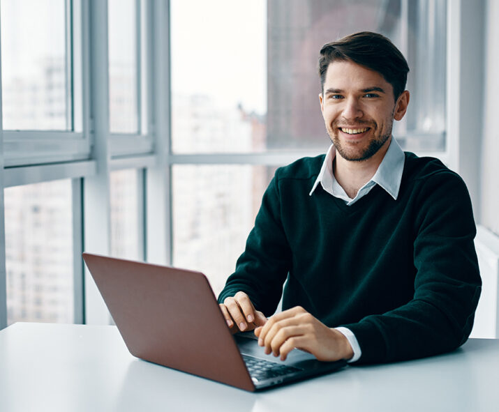 young man with laptop business suit working office home background window interviewing online